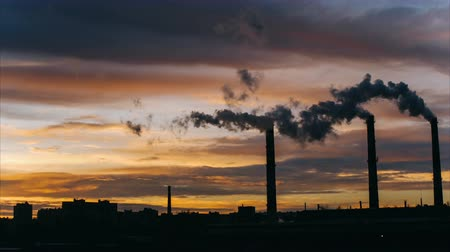 dioxid : Smoke from high industrial pipes at sunrise against the backdrop of the urban environment, environmental pollution, timelapse