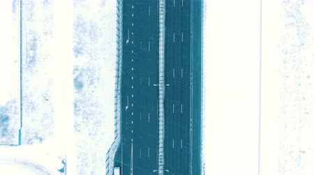 vertically : Aerial view vertically down the highway in winter in snowfall, cars driving on the highway
