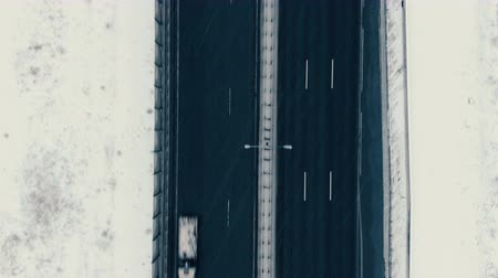 вертикально : Aerial view vertically down the highway in winter, cars drive along the road