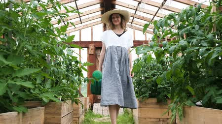watering can : Woman in a straw hat and dress goes to the greenhouse with a watering can