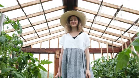 watering can : Smiling woman farmer in a straw hat and dress goes to the greenhouse with a watering can