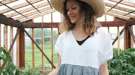 cheirando : Farmer in a straw hat and dress goes to the greenhouse, sniffing leaves and dancing circling