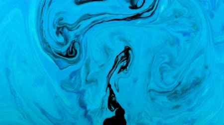 akvarell : Ink psychedelic black paints mixed in abstract patterns in blue liquid Stock mozgókép