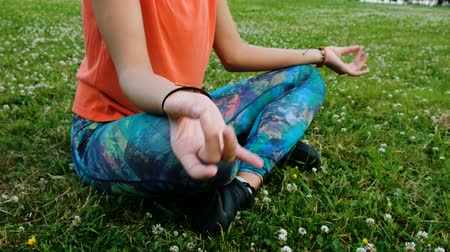 meditál : Woman meditates and doing yoga folds her hands in namaste sitting in the lotus position close up on the grass in a city park in nature Stock mozgókép