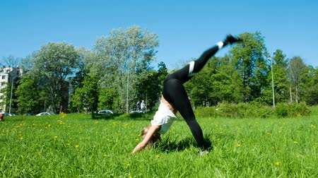 sznurek : Girl is engaged in fitness in nature, the girl gymnast lifts her leg up in the city park, slow motion