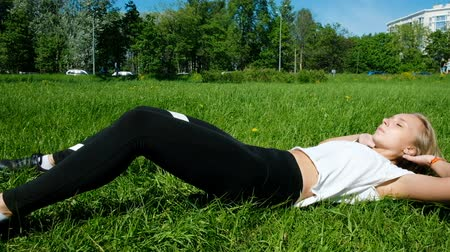 buikspieren : Athlete engaged in fitness in nature - shakes the abdominal muscles, slow motion