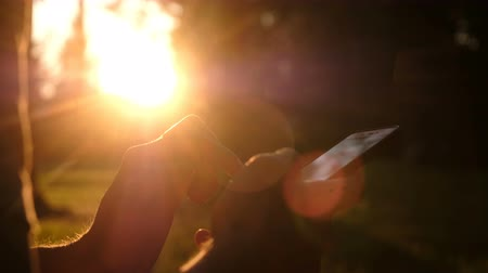 levelezés : Man using smartphone. Close up shot of man hands with mobile on sunset. Relax, nature concept. Stock mozgókép