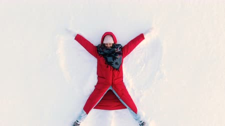 snow angel : Aerial camera moves out from woman lying in snow and making snow angel