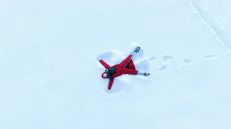 takes : Girl in a red down coat making a snow angel. Aerial, camera rises up in a spiral, top view Stock Footage