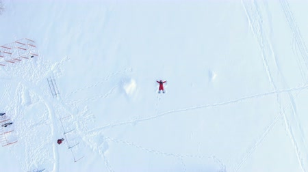 snow angel : Aerial camera rises up, a top view of a girl in a red fluff lying and making a snow angel