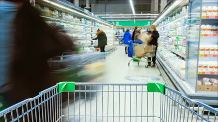 lista de chequeo : Timelapse - shopping trolley stands on the background of blurred customers in the aisle, people choose products Archivo de Video