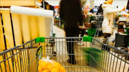 koszyk zakupy : Time-lapse speed shopping trolley rides to the supermarket and filled with food, shelving and blurred buyers