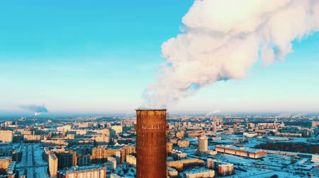 on site research : Aerial view of a smoking pipe of a thermal power plant at sunset