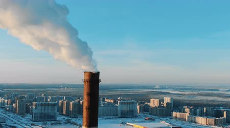 pipe tube : Aerial view of smoking chimneys in a residential area of the city at sunset in winter