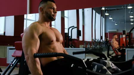 quadriceps : Bodybuilder trains the legs, medium plan. Man doing exercise with weightlifting machine in fitness center. Stock Footage