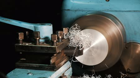área de trabalho : Engineer on a lathe works with an aluminum block, metal chips fly in slow motion