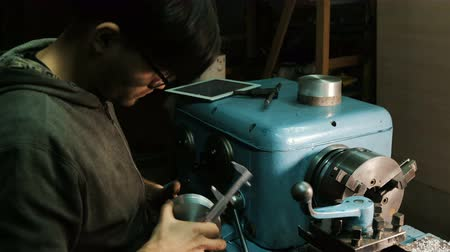 aluminio : Man looks at a drawing on an electronic tablet, checks the dimensions of the parts using a caliper. Manufacturing parts on a lathe.
