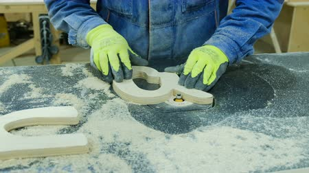 raggio : Worker removes chamfer radius cutter in a furniture factory. Manufacture of wooden furniture