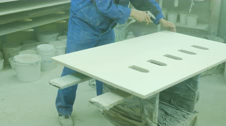 polido : Worker dusting a sheet of plywood before painting. Factory for the production of wooden furniture