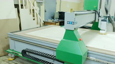 controlli : Automatic woodworking machine cuts out details on a wooden panel, modern woodworking machine cnc