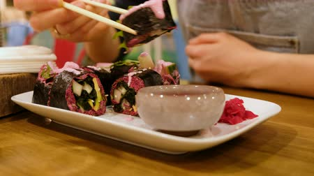 vegetarianismo : Girl in the cafe eats raw food vegetable rolls, closeup Vídeos