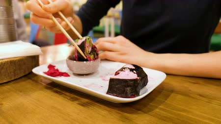 нори : Girl in a vegetarian cafe eats raw food rolls from vegetables