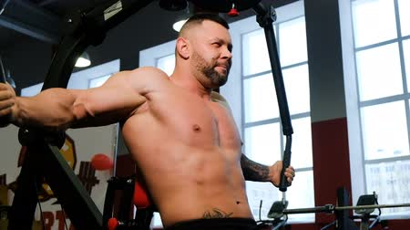 seis : Strong bodybuilder working out in the gym. Weightlifter trains chest muscles on the simulator