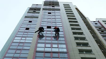 brushing : Men wash windows, wash windows on a skyscraper, work as a climber Stock Footage