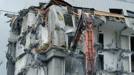 demolishing : Excavator destroys the old building. Demolition work, pieces of concrete and reinforcement fall down