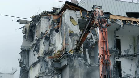 demolition : Excavator destroys the old building. Demolition work, pieces of concrete and reinforcement fall down