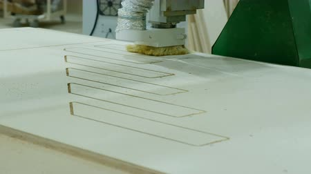 controlli : Modern woodworking machine in action. Cuts curly pieces from plywood sheet. Production of wooden furniture