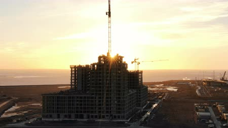 reinforced concrete : Flying over the construction site, the work of construction cranes and workers at sunset, aerial view
