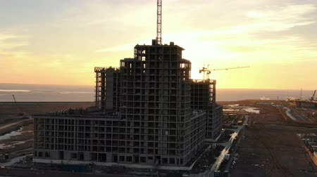 cova : Aerial view construction of multi-storey building with construction cranes at sunset Stock Footage