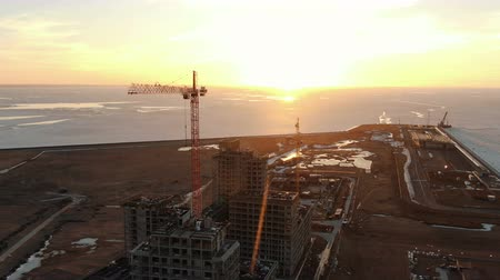 reinforced : Flying around a construction crane and construction site at sunset, shooting from a drone
