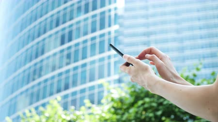переписка : Womens hands use a smartphone on the background of a glass business center and green trees