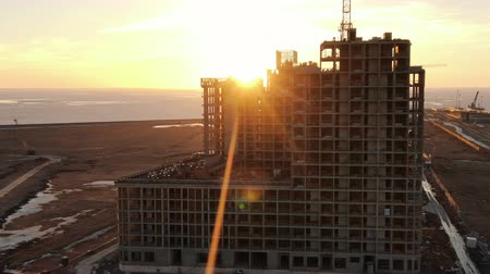 Flying of the construction of a multi-storey building on the background of sunset rays on the seashore Filmati Stock