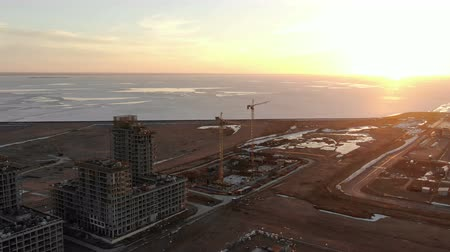 Flying over construction sites on the sea at sunset, aerial shot