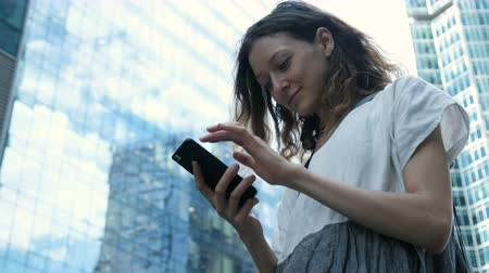tür : Girl uses internet on a smartphone typing text on the street against the background of skyscrapers in the business center Stok Video