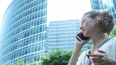 gesticulation : Business woman talking on the phone and gesticulating with hand on the background of skyscrapers Stock Footage