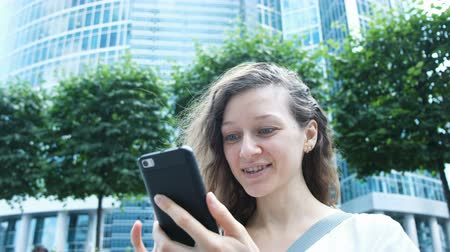 intrigue : Woman emotionally looking into the phone - surprise on the background of skyscrapers