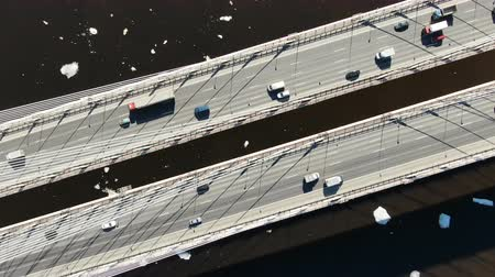 interscambio : Aerial view of trucks and cars driving on a cable-stayed bridge over the river