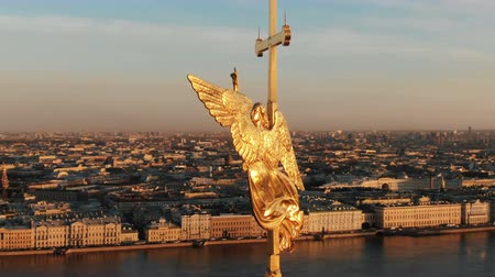peter and paul fortress : Flying around an angel on spire of Peter and Paul Fortress at sunset, close-up. Panorama of historical center of St. Petersburg Stock Footage
