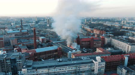 extinguishing : Aerial view of a fire in the building, firefighters extinguish the fire. The roof of the house in flames, there is black smoke.