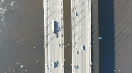 Aerial shooting, top view over a cable-stayedbridge over the river, spring ice floats on water