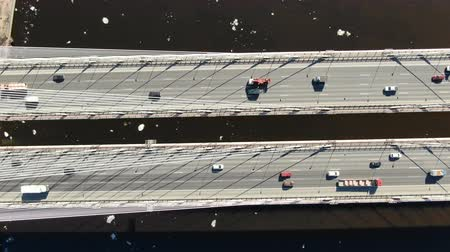 Cars drive on cable-stayed bridge over the river, aerial view, camera movement Stock Footage