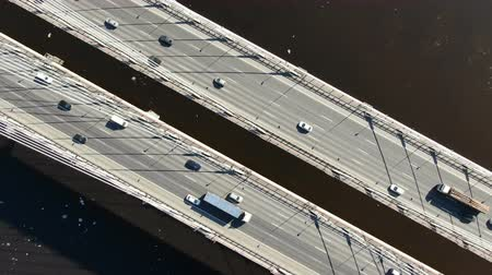 Aerial shooting over the cable-stayed bridge over the river, zoom in above the cars