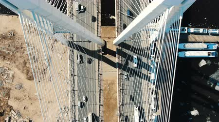 Aerial shooting over the cable bridge structure, cars driving over the bridge