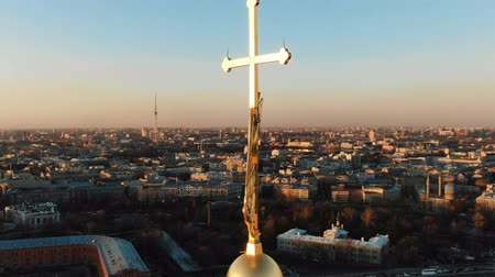 Aerial flying around an angel on spire of Peter and Paul Fortress at sunset, close-up. Historical panorama of St. Petersburg Stock Footage