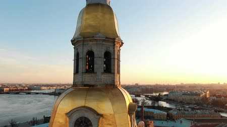 Aerial shoot around the bell tower of the Peter and Paul Fortress at sunset - in the historical center of St. Petersburg