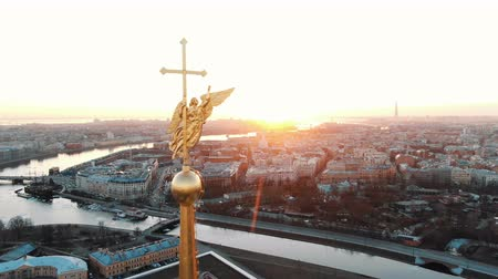 The span of the angel on the steeple in the Peter and Paul Fortress at sunset - aerial shooting of the historical center of St. Petersburg Stock Footage